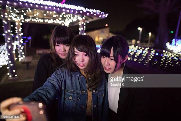 Three young girls taking selfie pictures in Christmas lights