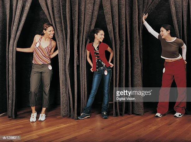 Three Young Girls Trying on Clothing By a Curtains in a Changing Room in a Clothes Shop