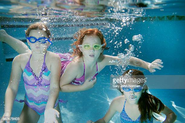 Three young girls underwater in pool.
