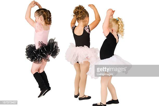Three young girls wearing tutus and dancing
