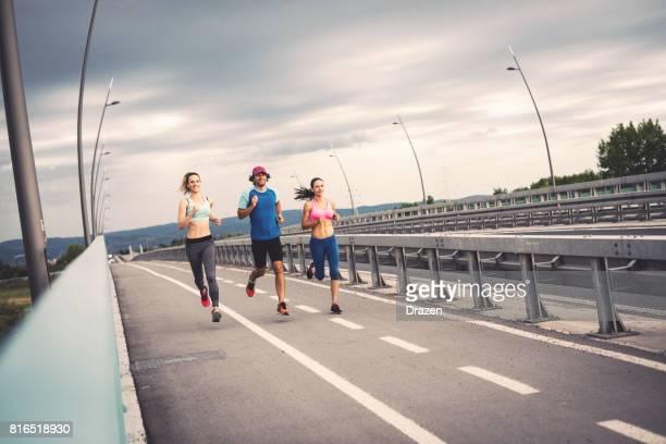 Drei junge gut aussehende Menschen Joggen in der Nähe Autobahn