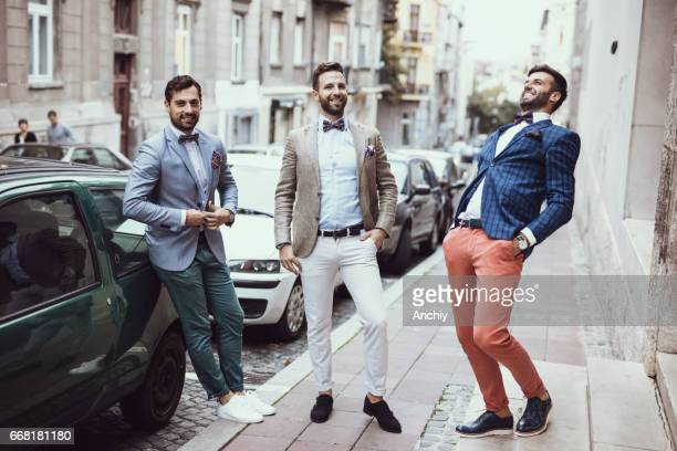 Three young good looking tailors laughing on the street