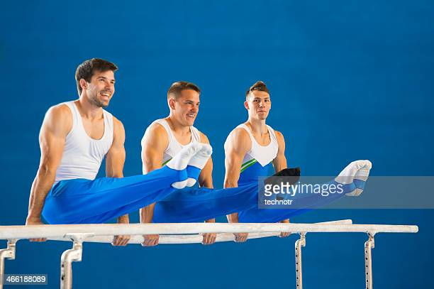 three young gymnasts posing on the parallel bars - artistic gymnastics stock pictures, royalty-free photos & images