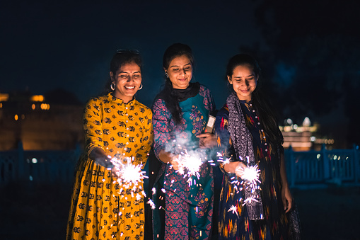 Three young Indian women with bengal fireworks, Udaipur, India 1176811104