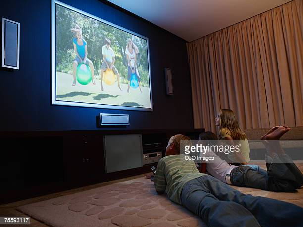Three young kids watching a large wall television