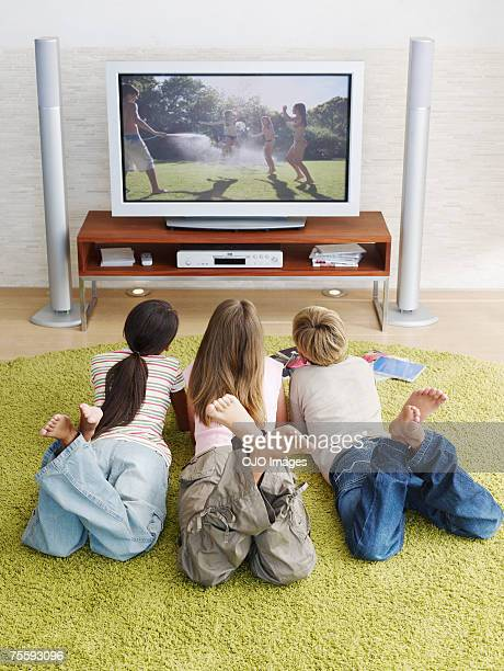 Three young kids watching television