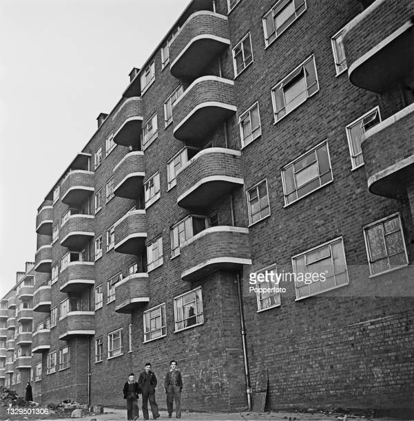 Three young lads walk past a block of recently constructed tenement flats, built for working class families, in Liverpool, England during World War...
