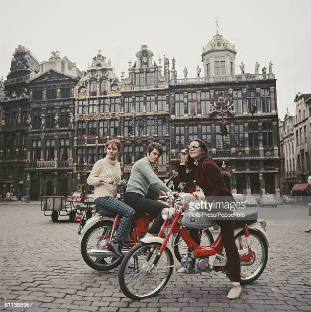 Three young male and female models sit on Honda motorcyles including variants of the Honda Sport 90 model in the Grand Place in Brussels Belgium in...