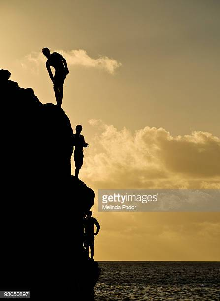 three young man standing on a rock - waimea bay stock photos and pictures