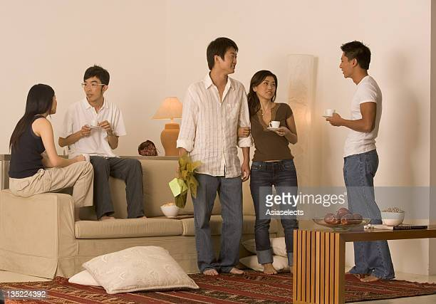 Three young men and two young women talking to each other in a living room