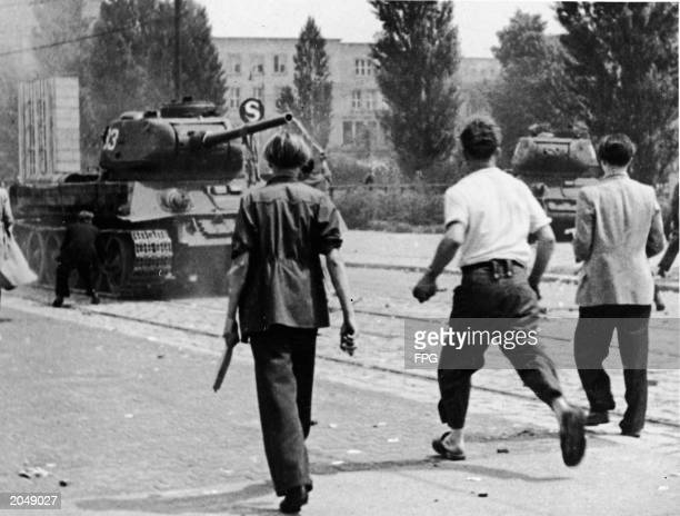 Three young men armed with sticks and stones approach a Soviet tank in a workers demonstration in which thousands rioted against the unfair labor...