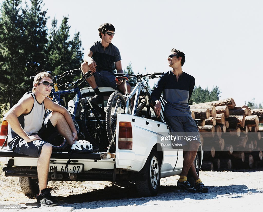 Three Young Men Around an Off Road Vehicle With Their Mountain Bikes : Stock Photo