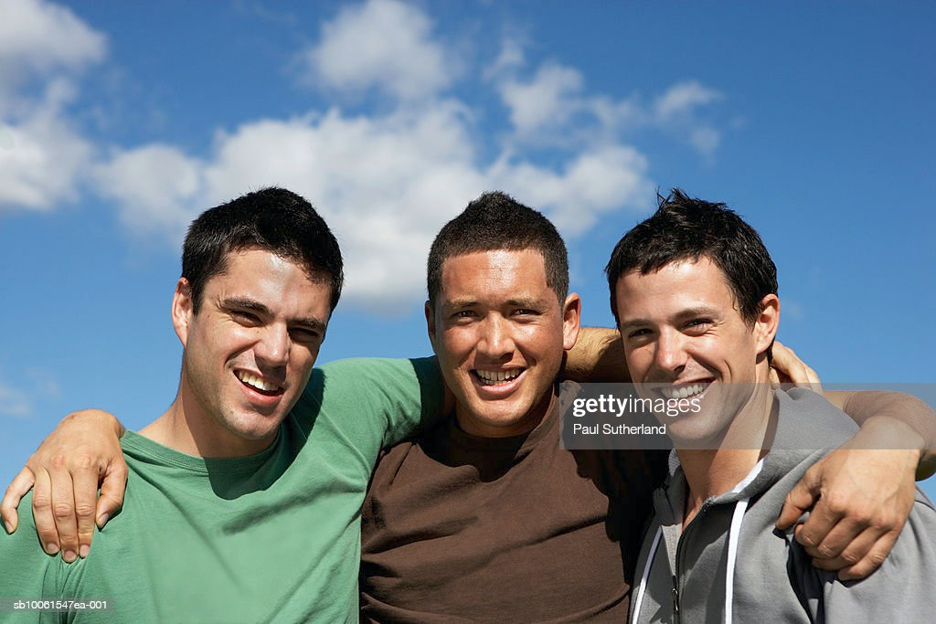 Three young men embracing outdoors, portrait, upper half : Stock Photo