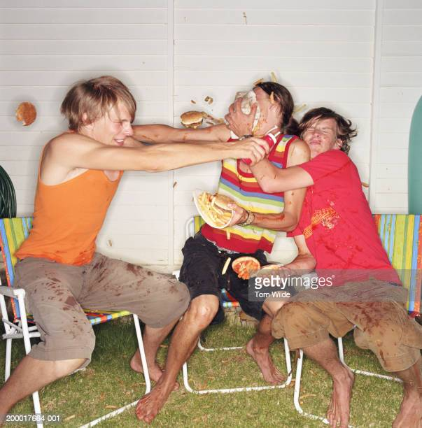 Three young men having food fight with burgers, chips and ketchup