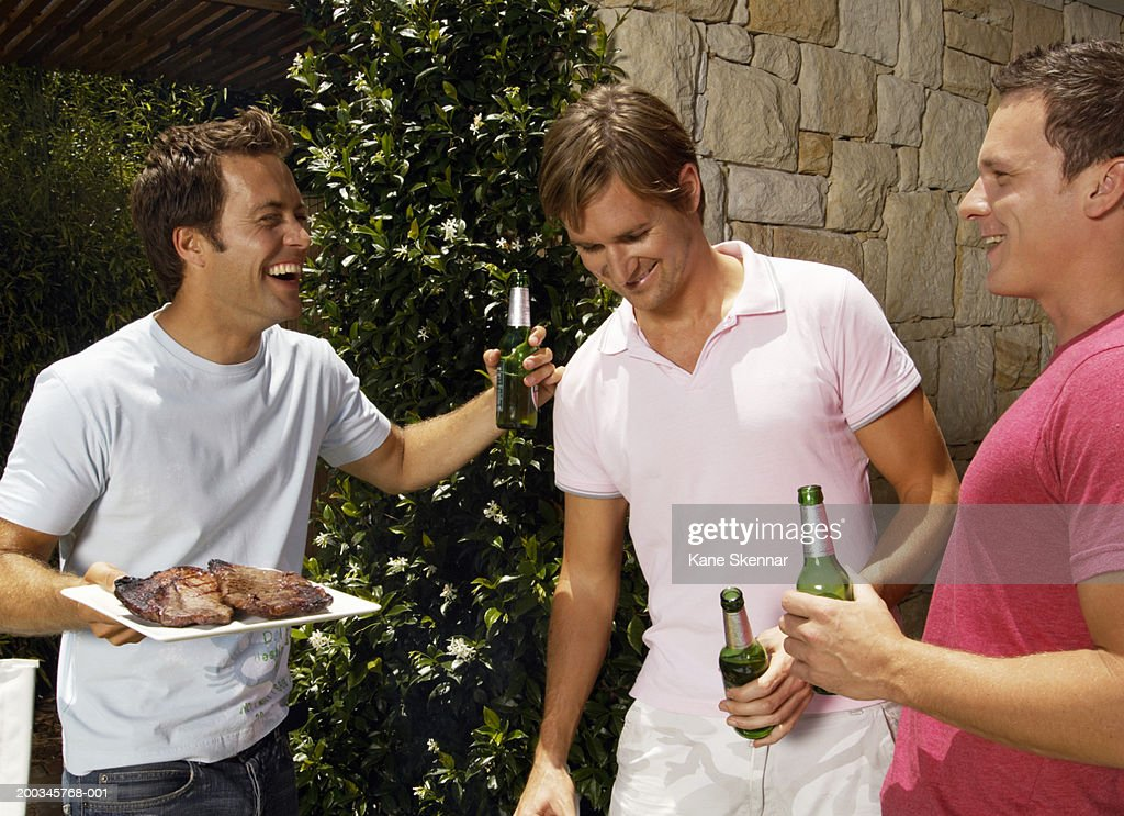 Three young men holding beer bottles and plate of meat, laughing : Stock Photo