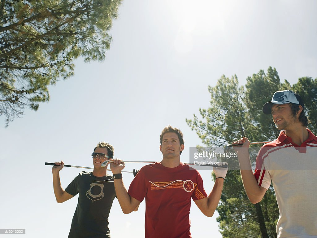 Three Young Men Holding Golf Clubs Across Their Shoulders : Stock Photo