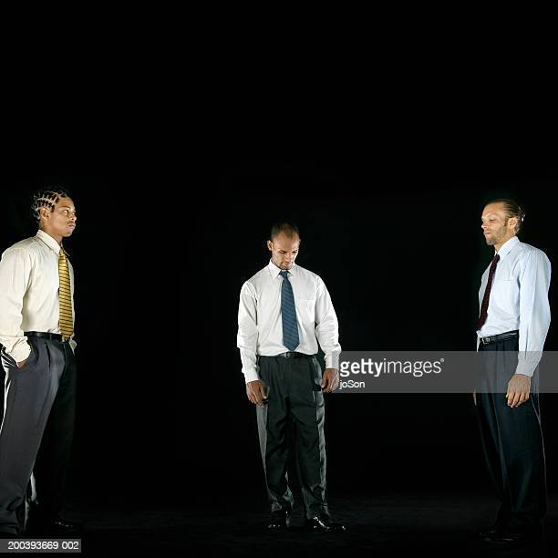 Three young men in business attire, looking serious