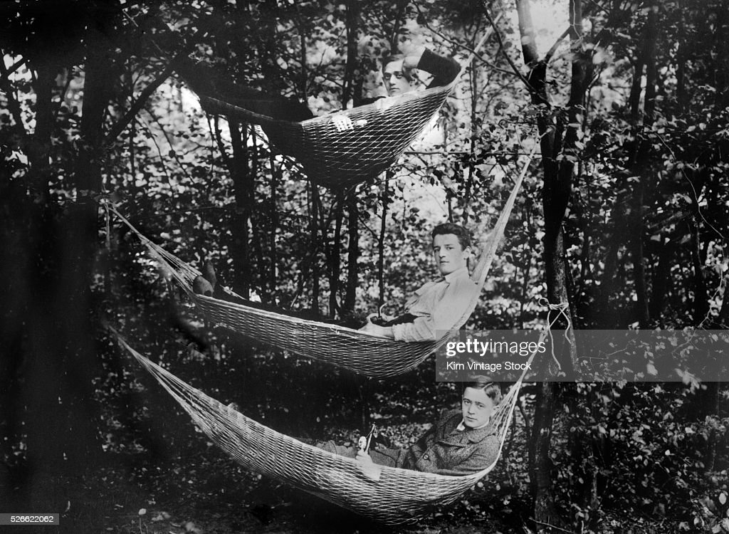 Three young men in hammocks in the woods, ca. 1930.