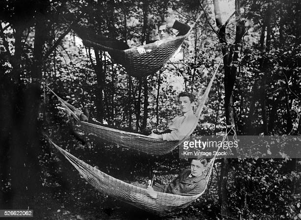 Three young men in hammocks in the woods ca 1930