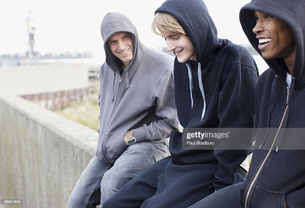 Three young men in hoodies sitting on wall : Stock Photo