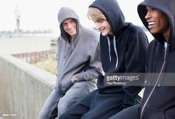 Three young men in hoodies sitting on wall