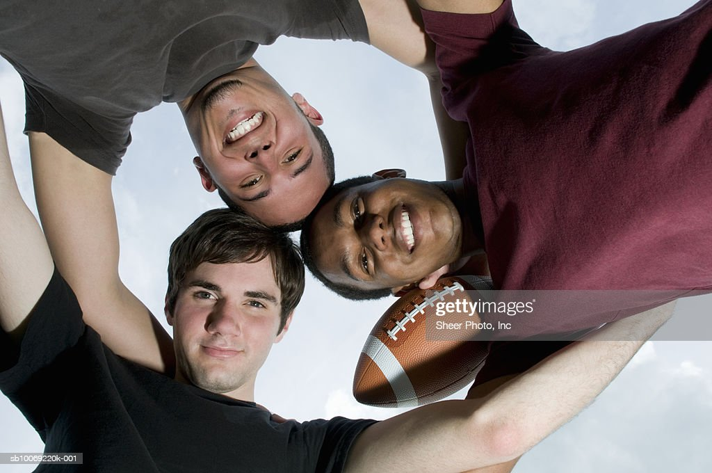 Three young men in huddle with football : Stockfoto