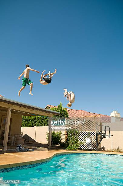 Three Young Men Jumping Off Roof Into Swimming Pool