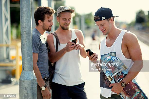 Three young men looking at mobile phones