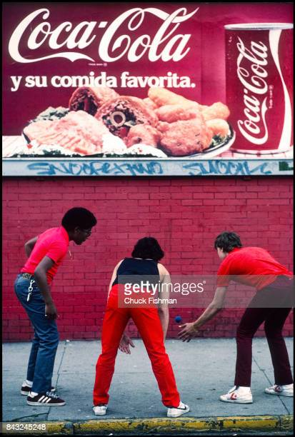 Three young men play hand ball against a red wall under a billboard in Spanish Harlem neighborhood New York New York mid 1980s