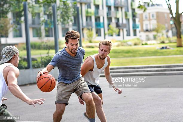 three young men playing basketball - dribbling sports stock pictures, royalty-free photos & images