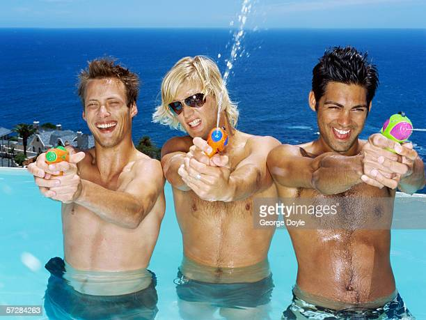 Three young men playing with water guns in a pool