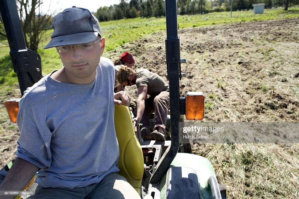 Three young men plowing field : Stockfoto
