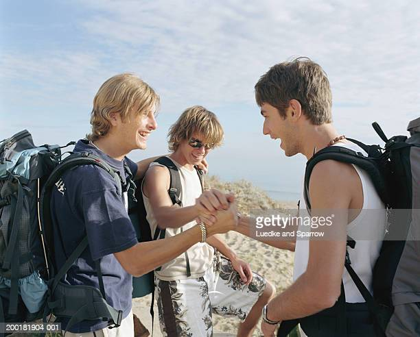 Three young men putting hands together, outdoors