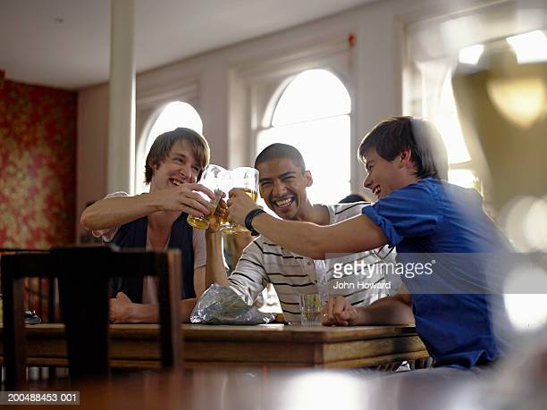 Three young men raising glasses in pub, smiling and laughing