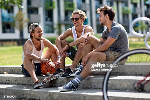 three young men sitting and chatting