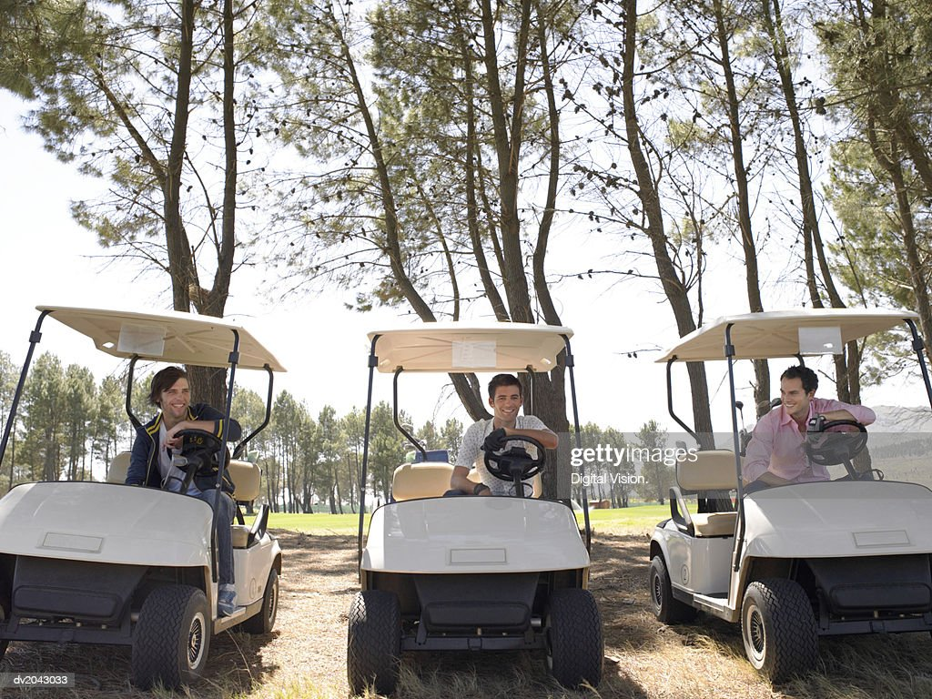 Three Young Men Sitting in Golf Buggies on a Golf Course : Stock Photo