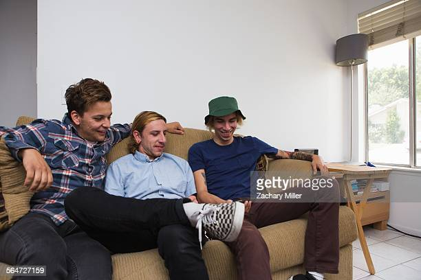 Three young men sitting on sofa, looking at smartphone