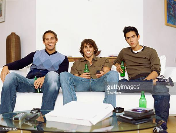 Three young men sitting on the sofa, drinking beer