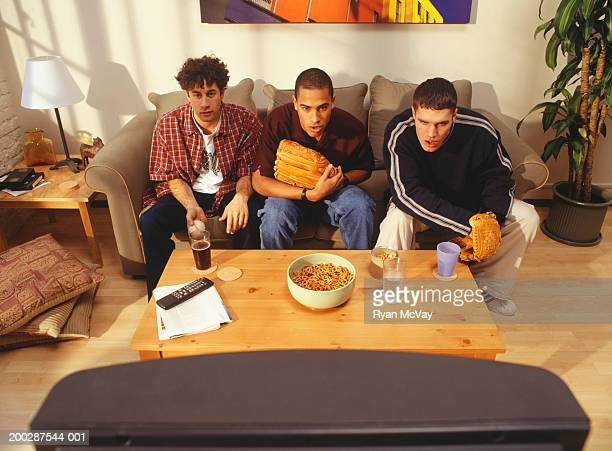 three young men sitting watching television in flat, elevated view - man cave stock pictures, royalty-free photos & images