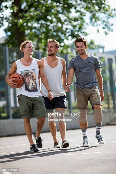 Three young men smiling and walking