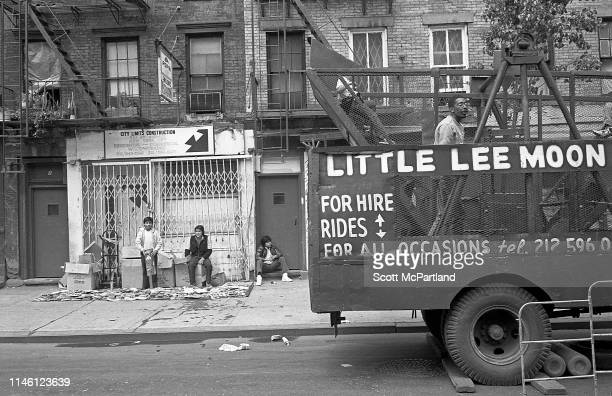 Three young men stand or sit outside an apartment building as a mobile 'pirate ship'style amusement ride is parked in front on the corner of West...