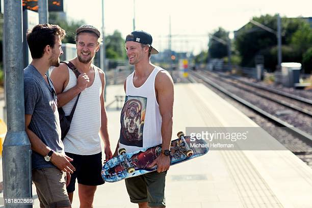 three young men standing next to train tracks