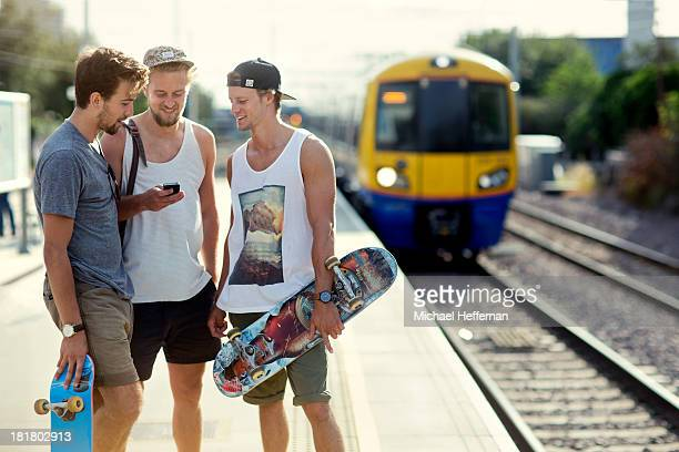 Three young men waiting for train
