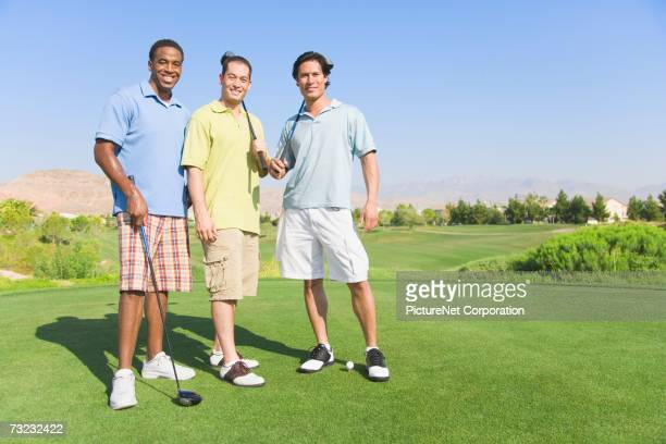 Three young men with golf clubs on golf course