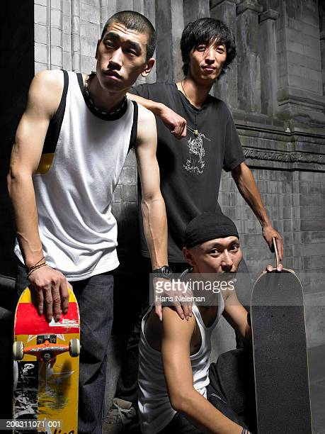 Three young men with skateboards, portrait, night
