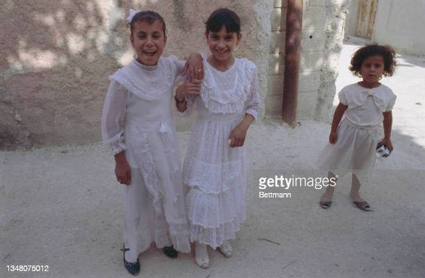 Three young Middle Eastern girls, two wearing white lace dresses, in Jerusalem, Israel, 1988.