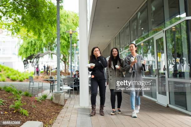 Three young millennial age female tech workers walk and hold lunch foods at the Googleplex headquarters of Google Inc in the Silicon Valley town of...