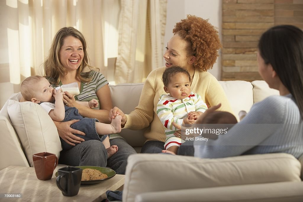 Three young mothers with babies on sofa : Stock Photo