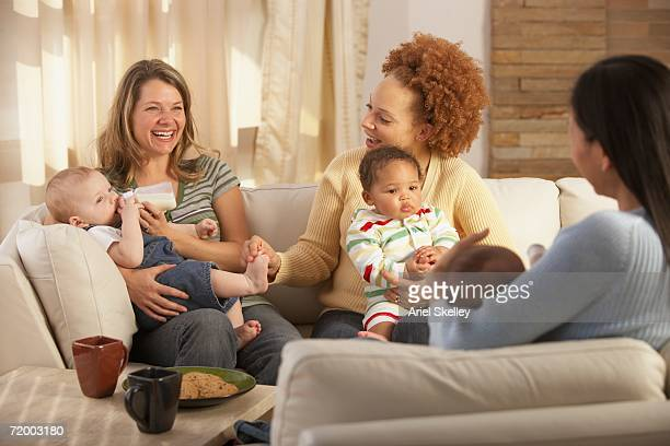 three young mothers with babies on sofa - black ginger baby stock photos and pictures