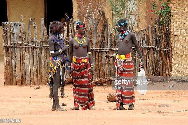 Three young native black women of the Bana / Bena tribe wearing traditional waistcloths / loincloths, Ethiopia, East Africa.